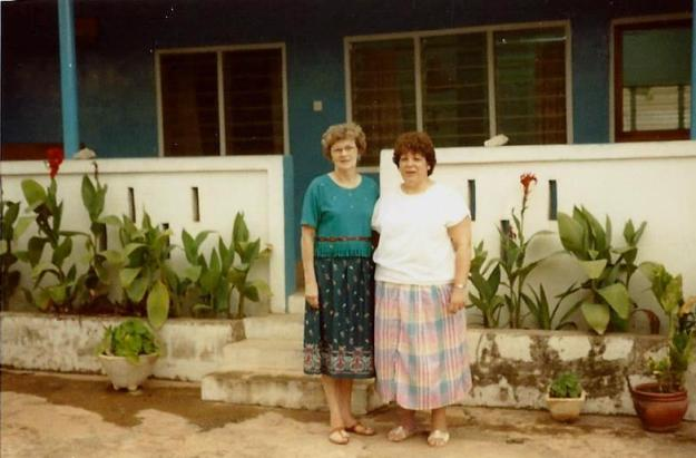 Mama with Avril, a Canadian nurse, in front of living quarters in the compound