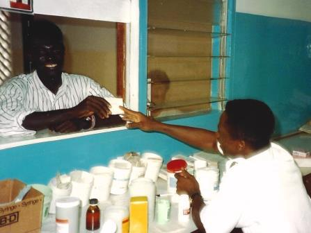 Pharmacy worker accepting prescription from a patient